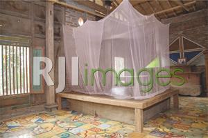 Kamar tidur utama dengan ranjang kayu lawasan